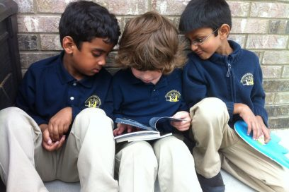 Three preschool aged boys reading a book.