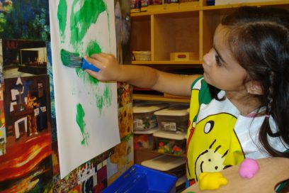 Preschool aged girl painting.