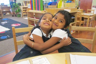 Two girls in a daycare setting hugging.