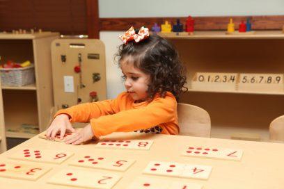 Preschool aged girl doing a math activity.