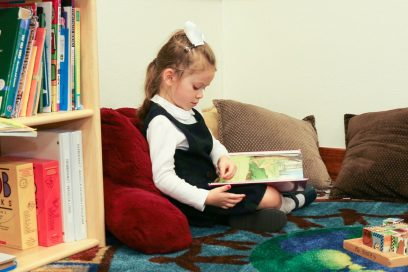 girl at daycare reading a book