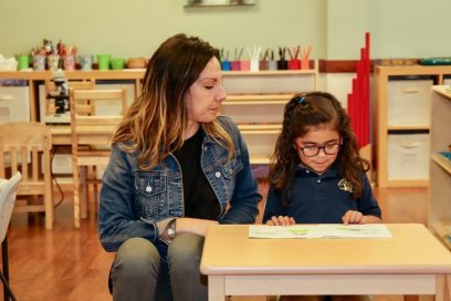 montessori teacher showing a girl how to read