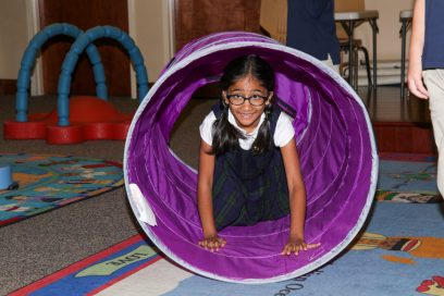 little girl crawling through a purple tunnel