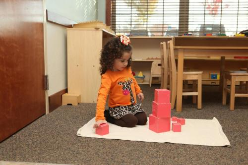 child in daycare stacking blocks